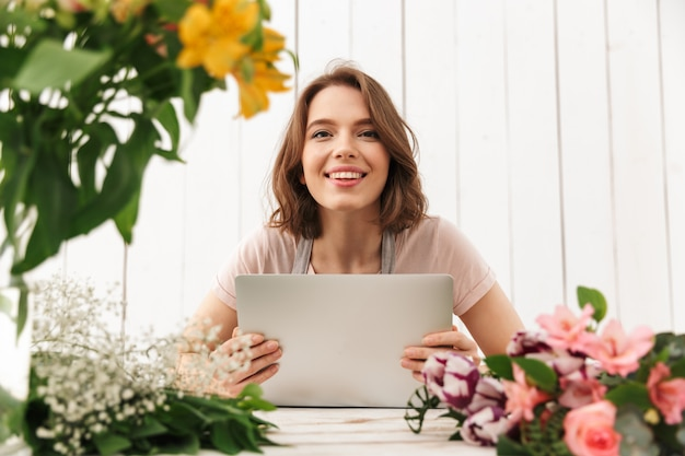 Cheerful florist lady standing with flowers using laptop computer.