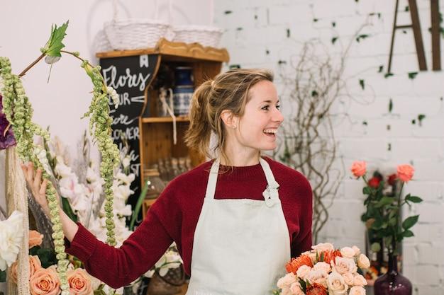 Веселый флорист, показывающий цветы в магазине