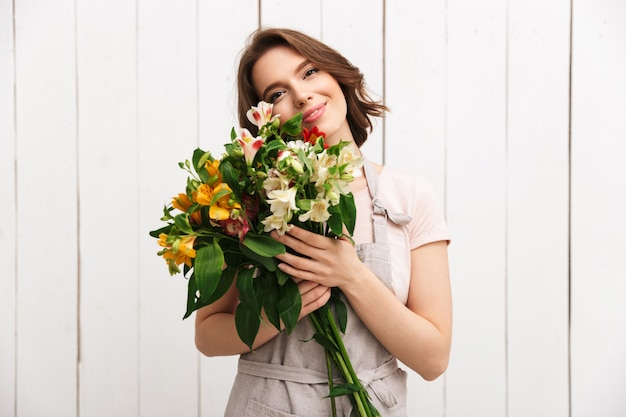 Cheerful florist woman standing with flowers