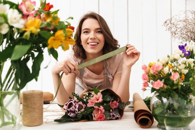 Cheerful florist woman with flowers in workshop