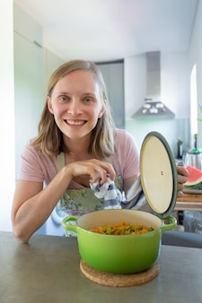 陽気な料理のブロガーが野菜の食事で鍋を開き、テーブルにもたれて、カメラにポーズをとって、笑顔で。垂直ショット。家庭料理のコンセプト