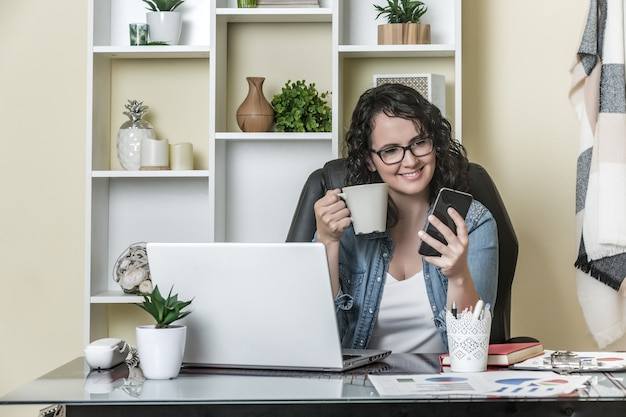Cheerful freelancer drinking hot beverage and using smartphone