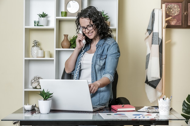 Cheerful freelancer speaking with client on phone