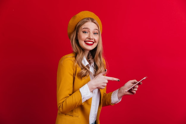 Веселая французская дама, указывая пальцем на смартфон. улыбающаяся блондинка в берете, стоя на красной стене