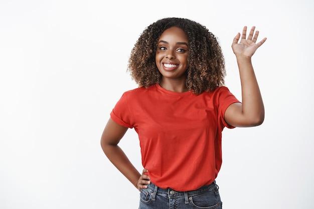 Веселая, дружелюбная афро-американская женщина с афро-прической, поднимающая руку и машущая фотоаппаратом с приятной улыбкой, как привет, привет или до свидания, приветствует вас, белая стена