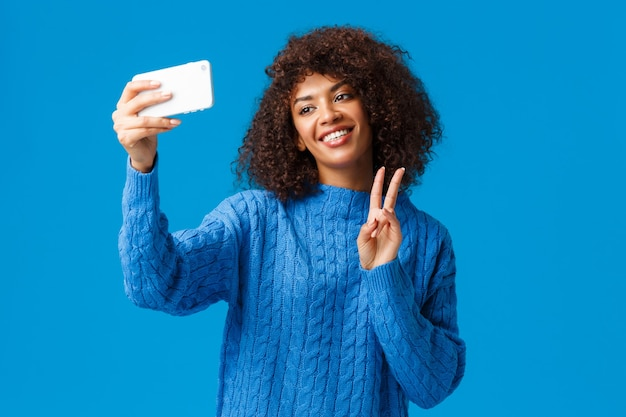 밝고 친절하고 귀여운 아프리카 계 미국인 여성 학생이 사진을 찍고 새 스마트 폰 앱에서 필터를 적용하고 셀카 틸트 헤드를 사랑스럽게 웃고 평화 제스처, 파란색 벽을 만듭니다.
