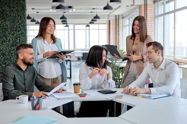 オフィスでビジネスプランの戦略を議論する陽気なフレンドリーなビジネスチーム