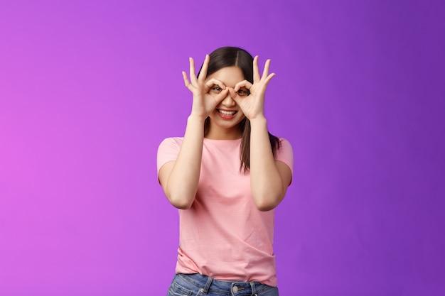 Веселая, дружелюбная беззаботная азиатская женщина, весело проводящая время, дурачится, показывает хорошие знаки на глазах, делает очки из пальцев, радостно улыбается, имитирует забавные эмоции, радуется фиолетовому фону.