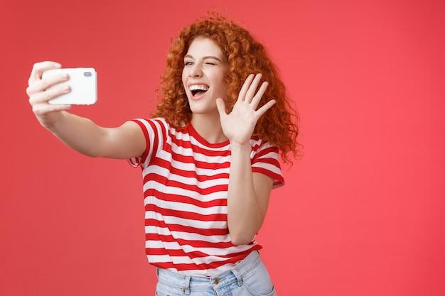 Веселая дружелюбная энергичная красавица рыжая кудрявая самка передает привет, машет ладонью, улыбается бр ...