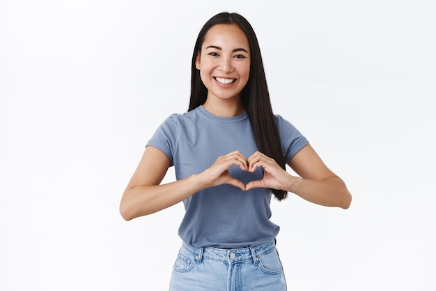 Cheerful, friendly and enthusiastic charming asian girlfriend saying i love you, showing heart sign and smiling, confess admiration, cherish relationship, happy valentines day, make surpise