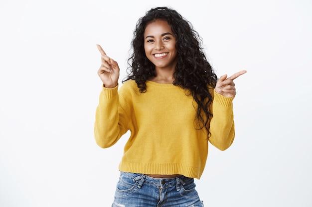 陽気なフレンドリーに見える魅力的な笑顔のアフリカ系アメリカ人の女の子が横向きの黄色いセーターで、2つの側面を示し、コピースペースを示す広告リンク、白い壁