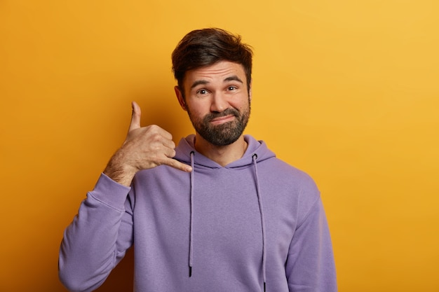 Cheerful friendly looking bearded man makes call me back gesture, pretends holding phone near ear, imitates call and mobile communication, demonstrates dial me sign, wears hoodie, poses indoor