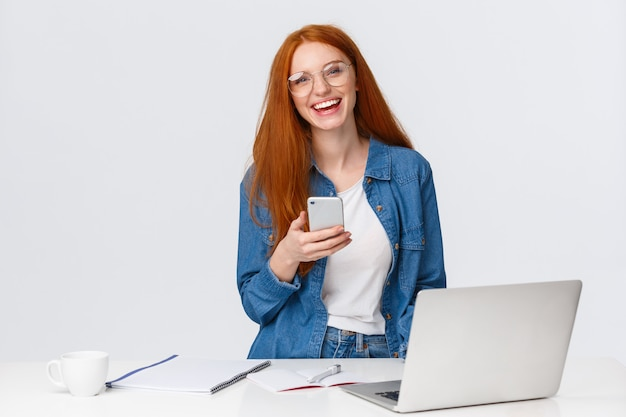 Cheerful, friendly-looking charismatic redhead female designer, freelancer with red foxy hair, glasses, laughing carefree, holding smartphone, working over project with laptop, drink coffee