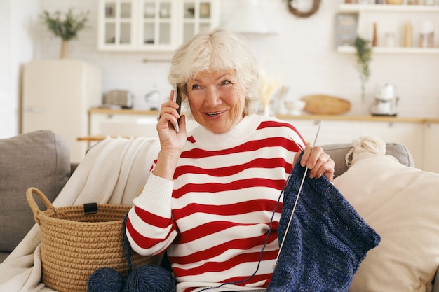 Cheerful friendly looking gray haired senior woman dressed in casual clothes sitting on sofa with needles and yard, having nice phone conversation with her old friend, gossiping, sharing latest news