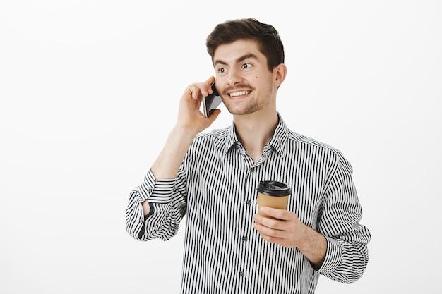 陽気で親しみのある男がマネージャーに電話して約束をつけ、スマートフォンで話し、コーヒーを飲み、広い笑顔で脇を見ます