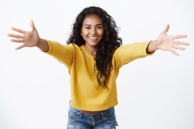 노란색 스웨터를 입은 쾌활하고 친근해 보이는 예쁜 여자, 따뜻한 환영으로 손을 벌리고, 즐겁게 웃고, 포옹하고, 친구에게 인사하고, 껴안고