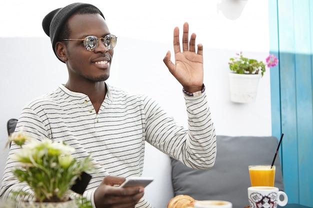 Cheerful friendly-looking young african american man wearing trendy headwear and sunglasses raising hand and gesturing while calling up waiter during breakfast at restaurant, using electronic gadget
