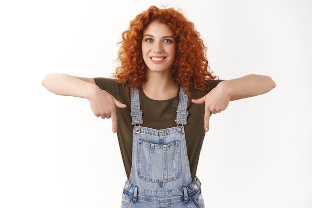 巻き毛の生姜のヘアカットが下の広告を表示し、笑顔で正面を見て幸せで、下を向いてアドバイスを与える、プロモーションコードを使用する、陽気なフレンドリーな明るい女性、トレンドビデオを見るのをお勧めします