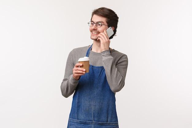 Веселый дружелюбный молодой работник мужского пола в переднике, имеющем разрыв, говорящий по телефону и пьющий кофе, улыбающийся, отводит взгляд, звоня другу, обсуждает вечеринку после его смены,