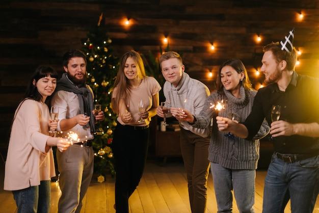 陽気な友達がシャンパングラスとベンガルのライトでポーズをとり、新年を祝っています。背景に花輪とクリスマスツリー。友達はクリスマスイブを祝っています。