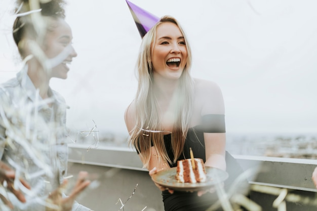 Cheerful friends celebrating a birthday party at a rooftop
