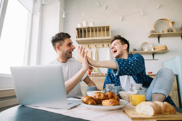 Cheerful friends clapping hands sitting in front of table with breakfast and laptop