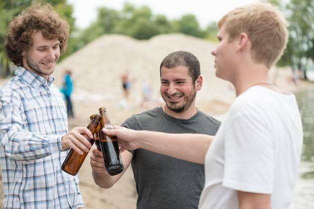 Cheerful friends clinking bottles on beach