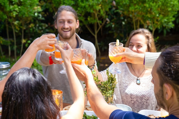 Cheerful friends clinking glasses outdoor