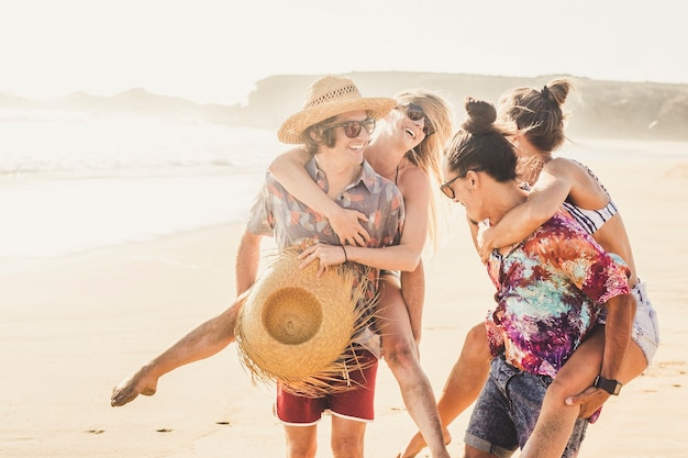 陽気な友達のカップルの女の子と男の子が一緒に夏休みのベラクで一緒に楽しんでいます-女性を運ぶ男性とみんなが笑顔でたくさん笑います