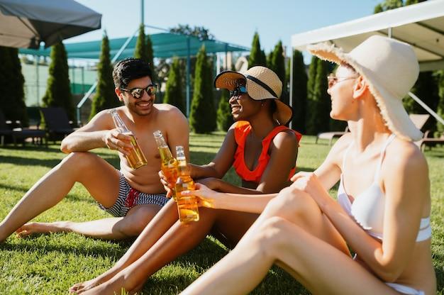 쾌활한 친구들은 수영장 근처에서 함께 맥주를 마십니다. 여름 방학에 즐거운 시간을 보내는 행복한 사람들, 야외 수영장에서 휴가 파티. 한 남자와 두 여자가 일광욕을 하고 있다
