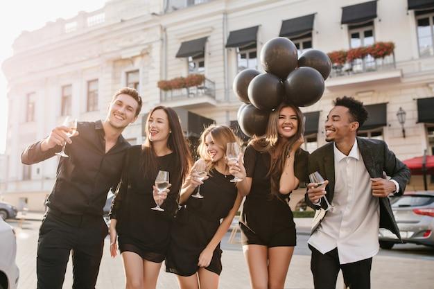 屋外のパーティーでシャンパンを飲む陽気な友達