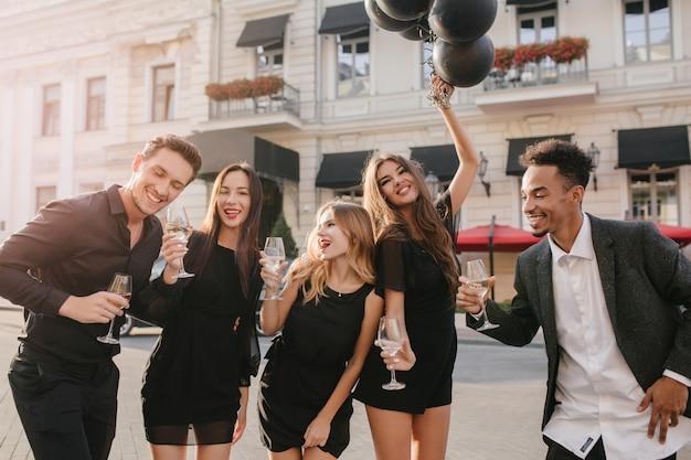 Веселые друзья пьют шампанское на вечеринке на открытом воздухе