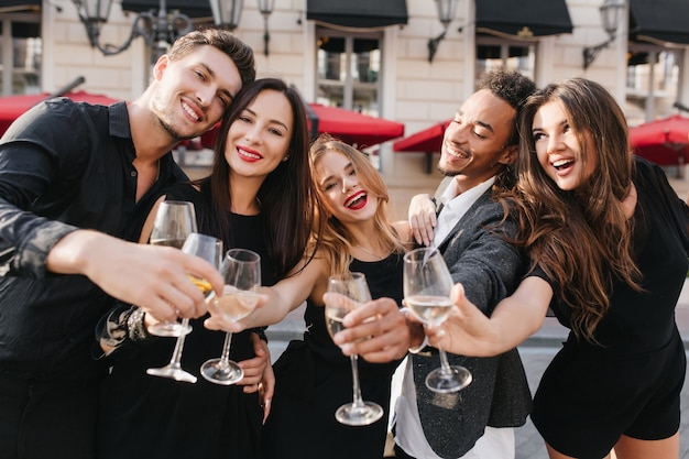 Cheerful friends drinking champagne at party outdoors