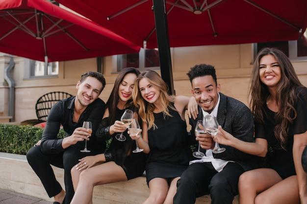 Amici allegri che bevono champagne alla festa all'aperto
