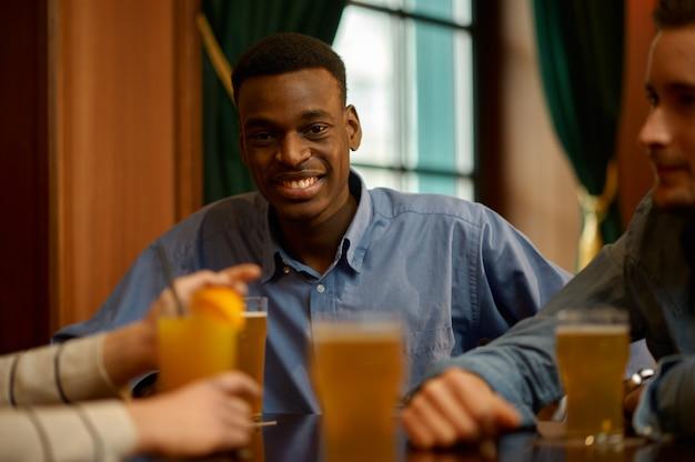 Веселые друзья пьют алкоголь и веселятся за столиком в баре. группа людей отдыхает в пабе, ночной образ жизни, дружба, празднование события
