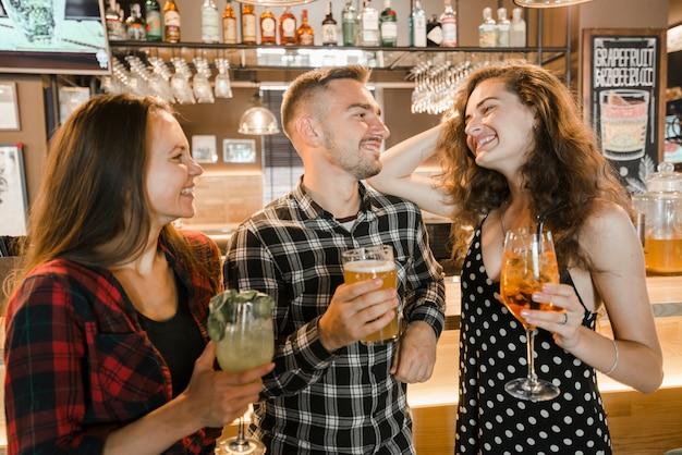 Cheerful friends enjoying evening drinks in the bar