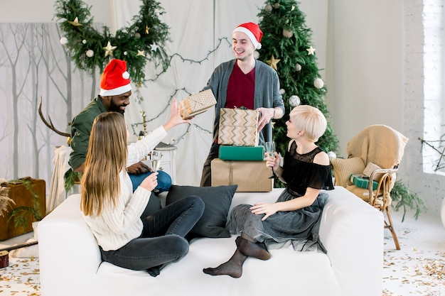 Cheerful friends exchanging presents at christmas eve