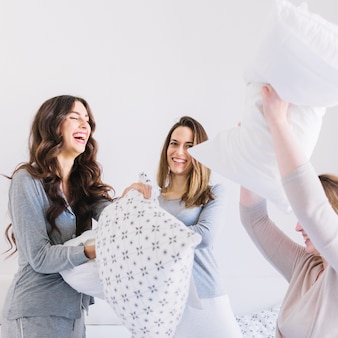 Cheerful friends fighting with pillows