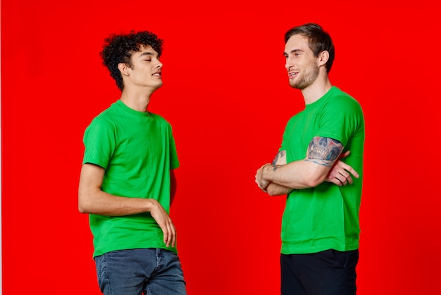 Cheerful friends in green tshirts hugs communication