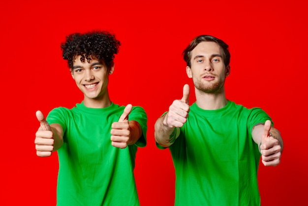手の感情の赤い背景で身振りで示す緑のtシャツの陽気な友達。高品質の写真