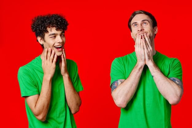 緑のtシャツを着た陽気な友達が感情の顔を保持します