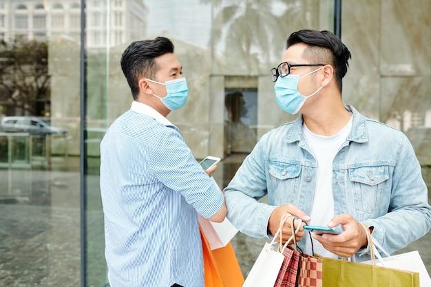 Веселые друзья в медицинских масках приветствуют друг друга локтями во время пандемии