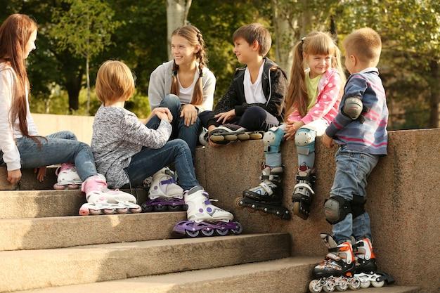 公園の境界線に座っているローラー スケートの陽気な友達
