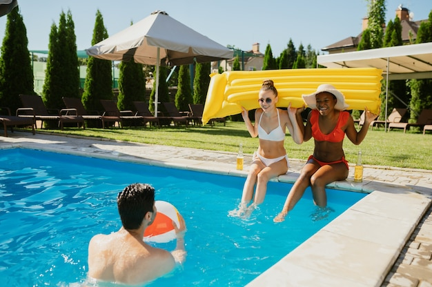Cheerful friends play with ball in the pool