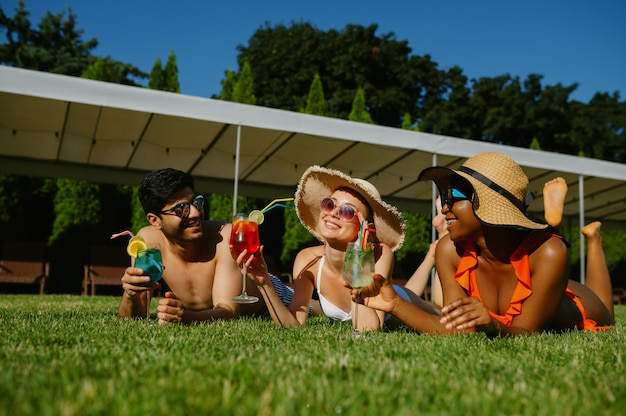 Cheerful friends rest on the grass near the pool