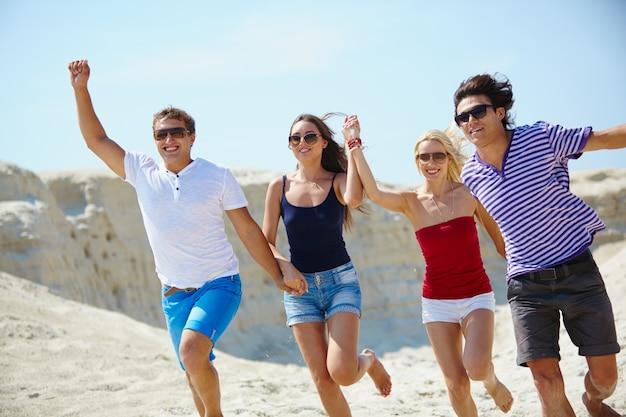 Cheerful friends running in the sand