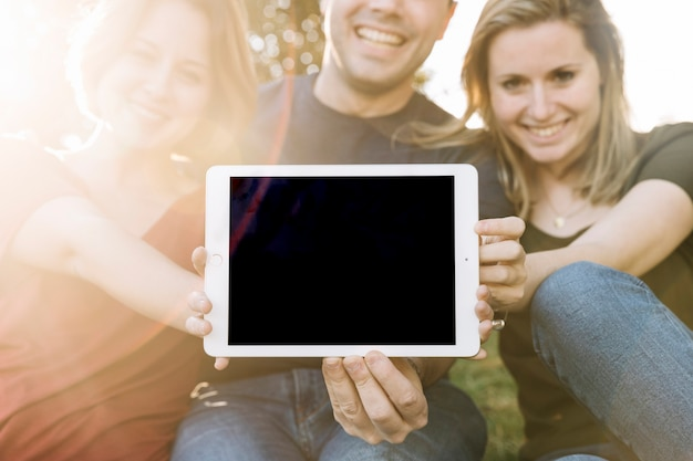 Cheerful friends showing tablet to camera