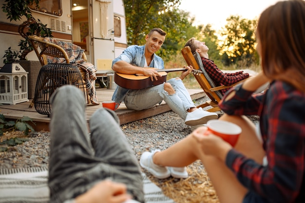 Cheerful friends sing songs with guitar on picnic at camping in the forest