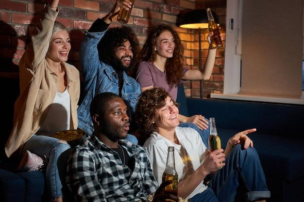 집에 앉아 텔레비전에서 축구 경기를 보는 쾌활한 친구. 가장 좋아하는 팀은 승리, 승리 개념입니다. 응원, 맥주, 휴식
