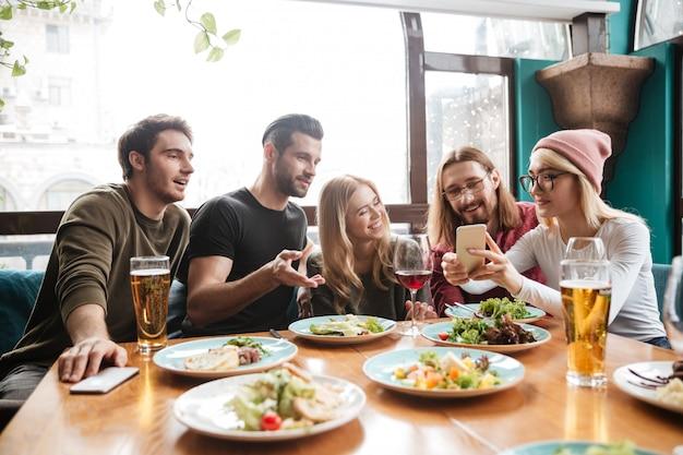 Веселые друзья сидят в кафе, разговаривают друг с другом.